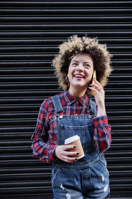 Mulher feliz segurando copo de café descartável ao falar no telefone inteligente na frente do obturador — Fotografia de Stock