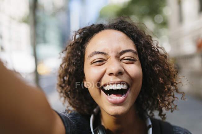 Rindo jovem mulher tomando selfie na cidade — Fotografia de Stock
