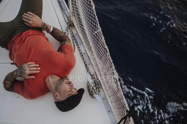 L'uomo hipster distoglie lo sguardo mentre giace sulla barca in mare — Foto stock