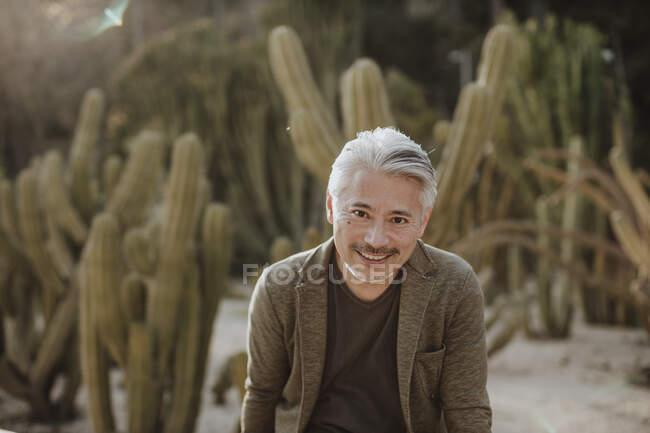 Sorrindo homem maduro com cacto jardim no fundo — Fotografia de Stock