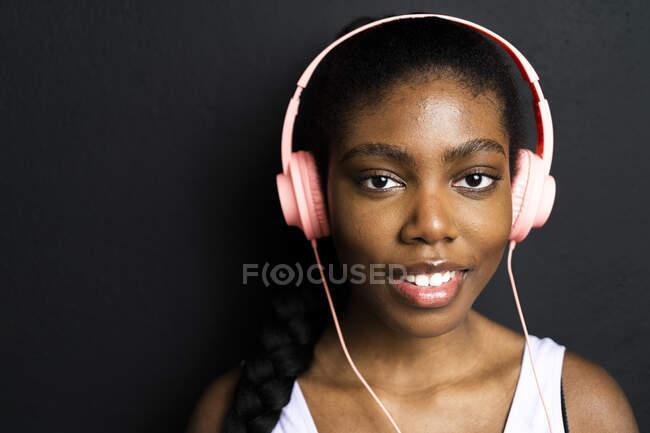 Mujer sonriente escuchando música a través de auriculares sobre fondo negro - foto de stock