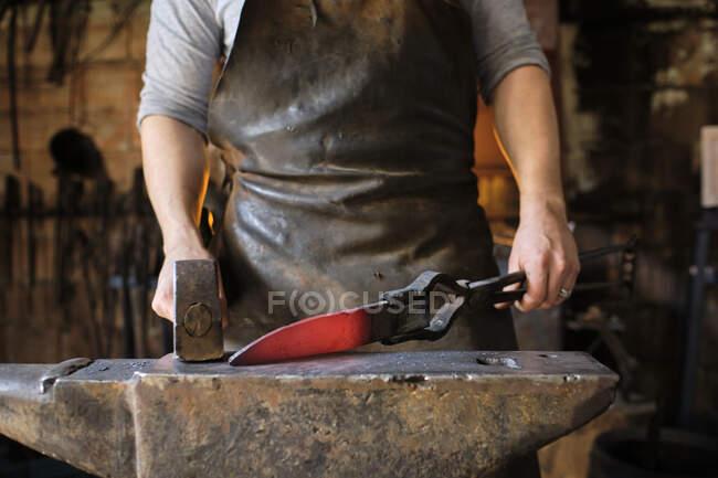 Блексміт робить ніж з металу на коварі в магазині коваля. — стокове фото