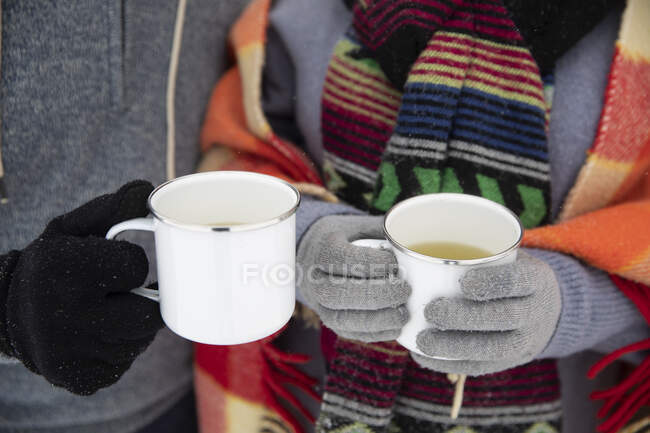 Couple holding mugs with tea during winter — Stock Photo