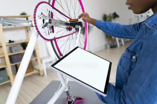 Молода жінка з цифровим планшетом ремонтує велосипед вдома. — стокове фото