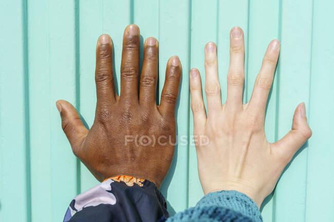 Manos de amigos multi-étnicos masculinos y femeninos en la pared turquesa - foto de stock