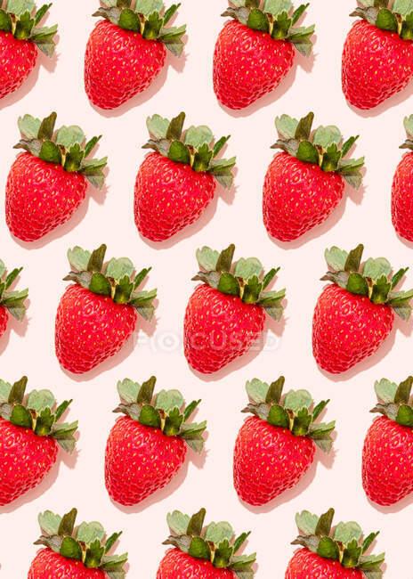 Modello di fragole mature fresche che si trovano sullo sfondo rosa chiaro — Foto stock