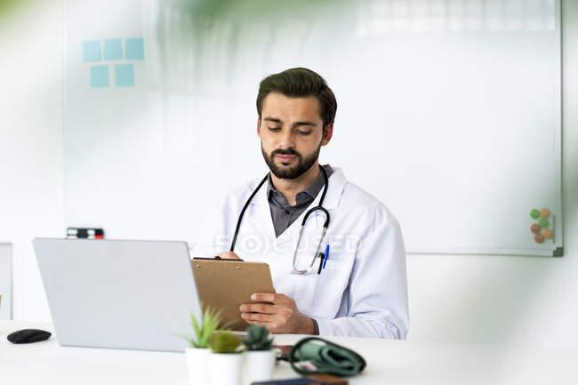 Hombre trabajador de la salud con portapapeles y portátil sentado en el escritorio - foto de stock