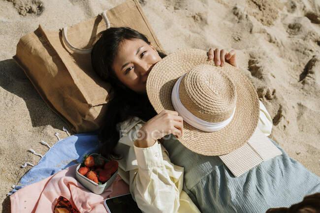 Donna con cappello sdraiata sulla sabbia in spiaggia durante la giornata di sole — Foto stock