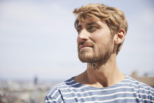 Красивый мужчина смотрит в сторону в солнечный день — стоковое фото