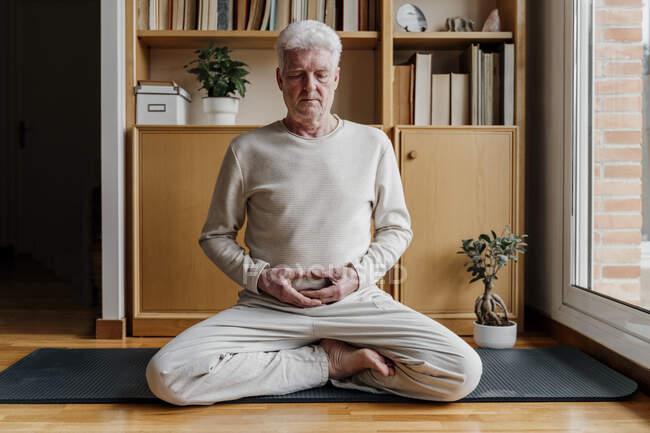 Старший медитирует, сидя дома со скрещенными ногами — стоковое фото