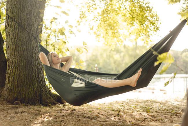 Mujer joven relajándose en hamaca junto al lago - foto de stock