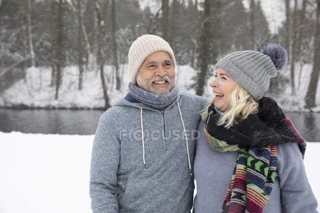 Cheerful woman looking at smiling man in park during winter — Stock Photo