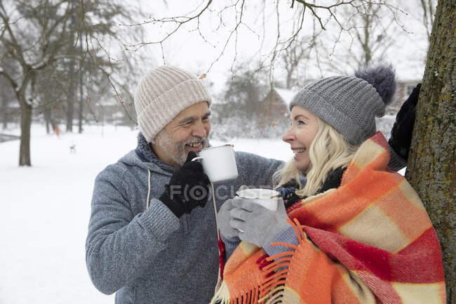 Smiling senior couple drinking tea in mug during winter — Stock Photo
