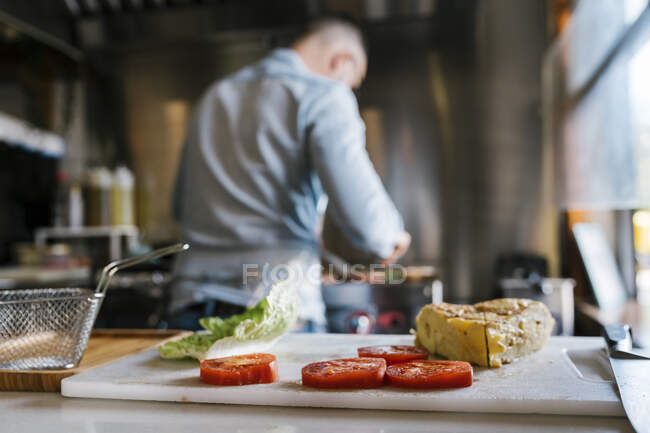 Sandwich and tomato slices on cutting board while chef cooking food in background at restaurant — Stock Photo