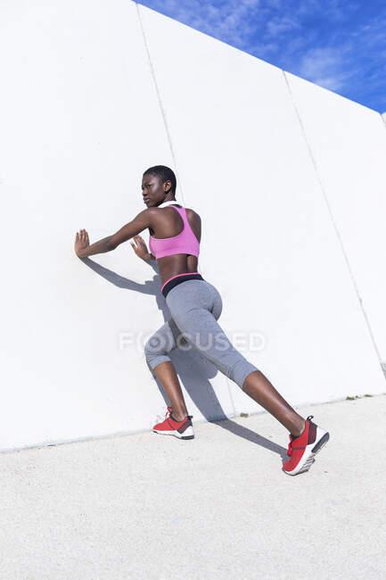 Подходит молодая женщина, растягивающая ноги, опираясь на белую стену — стоковое фото