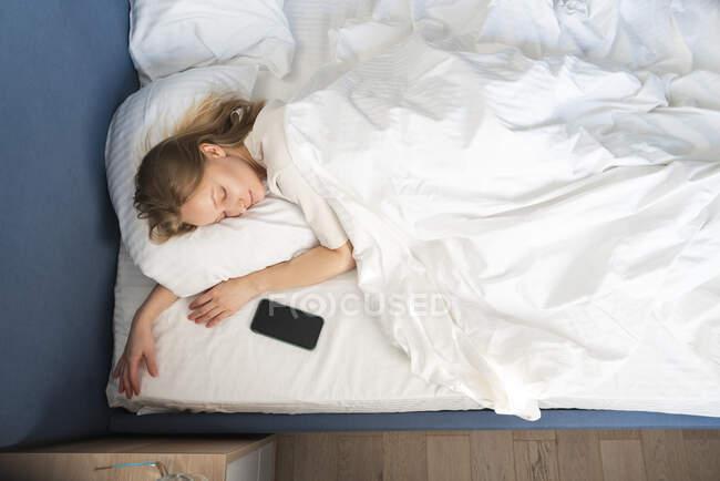 Donna che dorme dal telefono cellulare a letto a casa — Foto stock