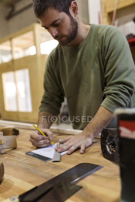 Tischler arbeitet in Werkstatt am Tisch — Stockfoto