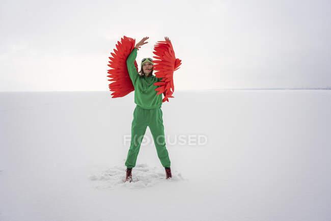 Mujer en traje de pájaro verde mirando hacia arriba mientras está de pie contra el cielo - foto de stock