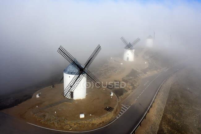 Spagna, Provincia di Toledo, Consuegra, Veduta aerea della strada di campagna che si estende oltre i mulini a vento storici durante la nebbia — Foto stock