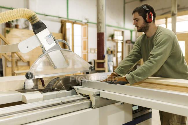 Tischler mit Ohrenschützer arbeitet in der Industrie an Tischkreissäge — Stockfoto
