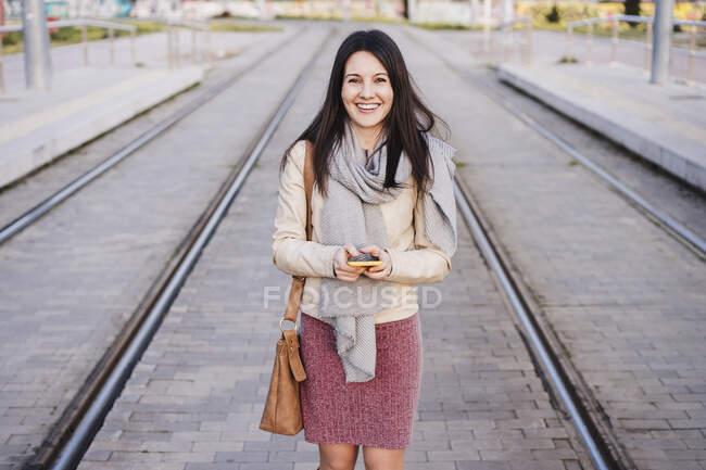 Mulher feliz com telefone inteligente em pé entre trilhos ferroviários — Fotografia de Stock
