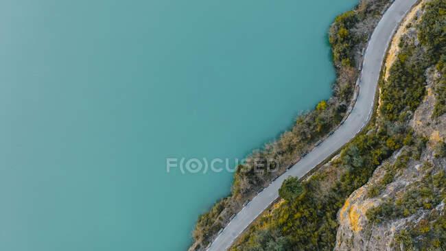 Veduta aerea della strada di campagna che si estende lungo la riva del lago turchese — Foto stock
