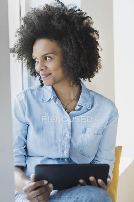 Lächelnde junge Frau, die zu Hause aus dem Fenster schaut — Stockfoto
