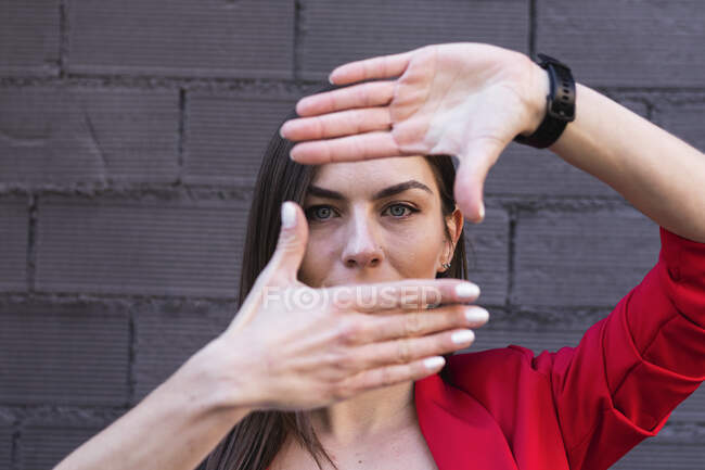 Businesswoman with gray eyes making finger frame against purple brick wall — Stock Photo