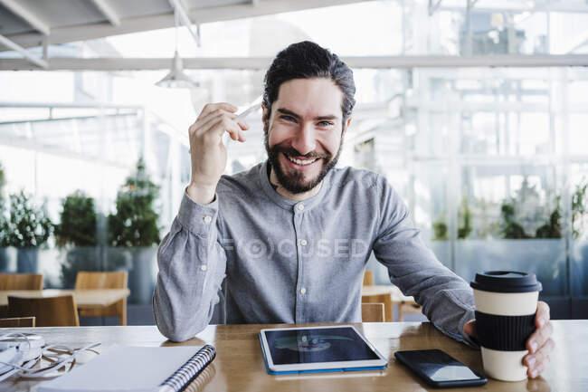 Улыбающийся мужчина-фрилансер с чашкой кофе многоразового использования по беспроводным технологиям в офисе — стоковое фото