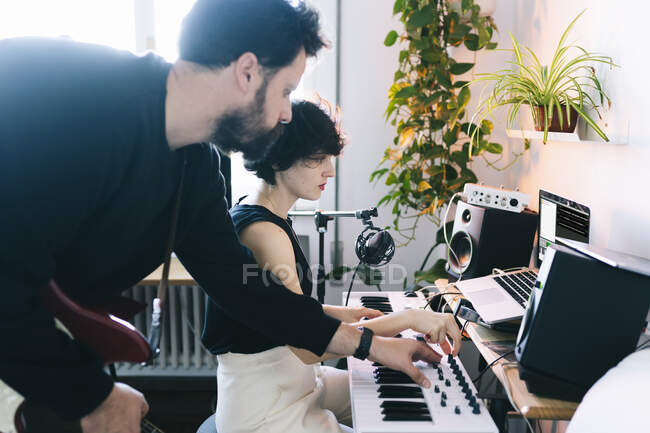Músico masculino ayudando a compositora femenina con piano eléctrico en estudio - foto de stock