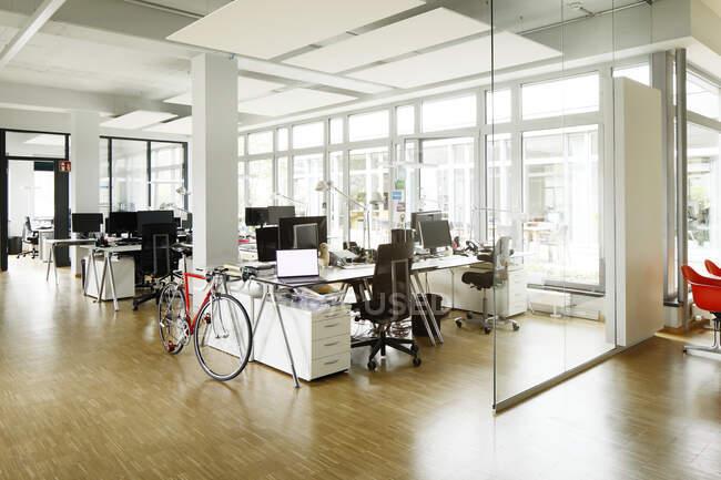 Велосипед за столом у відкритому офісі. — стокове фото