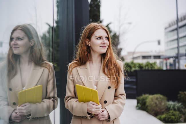 Femme souriante rêvant jour tout en tenant tablette numérique par verre — Photo de stock