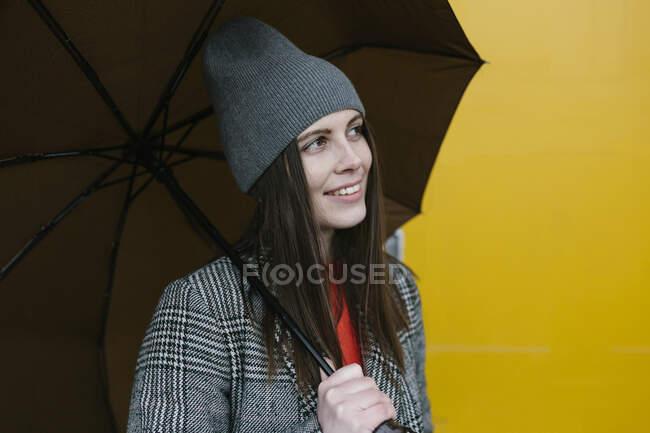 Жінка тримає парасольку біля жовтих дверей. — стокове фото