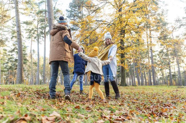 Играющие родители и дети держатся за руки во время игры в лесу — стоковое фото