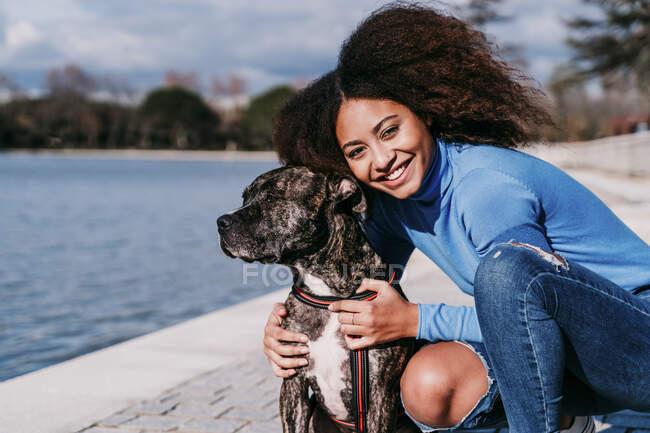 Sorridente capelli ricci donna accovacciata dal cane nella giornata di sole — Foto stock
