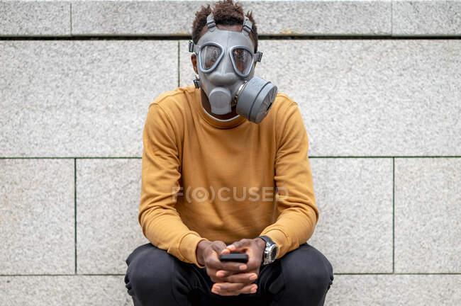 Jovem vestindo máscara de gás poluição sentado com telefone celular contra a parede — Fotografia de Stock
