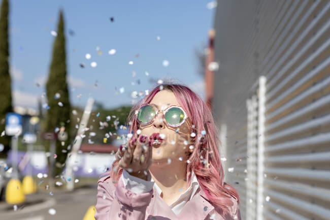 Giovane donna con capelli rosa e giacca che soffia corietti nella giornata di sole — Foto stock