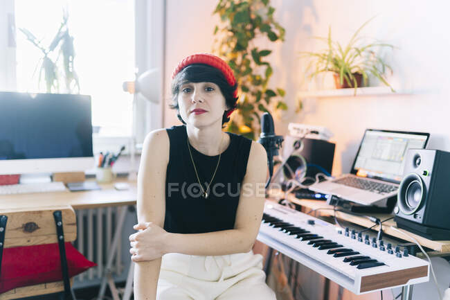 Female music composer wearing knit hat while sitting by electric piano in studio — Stock Photo