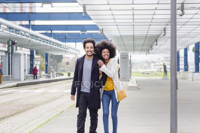 Novio y novia caminando juntos en la estación de tren - foto de stock