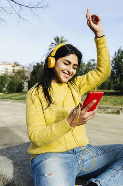 Mujer sonriente con auriculares bailando mientras sostiene el teléfono móvil en el parque - foto de stock
