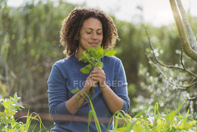 Жінка з закритими очима пахне свіжим органічним м'яти в саду — стокове фото