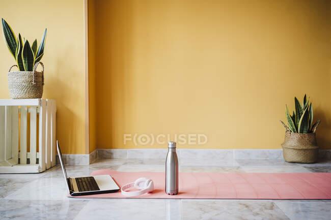 Computer portatile, bottiglia d'acqua e cuffie sul tappetino per esercizi a casa — Foto stock