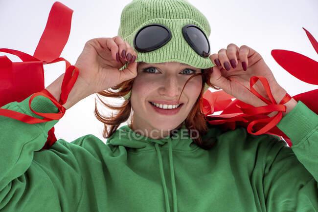 Mujer sonriente con ojos grises sosteniendo sombrero de punto contra el cielo - foto de stock