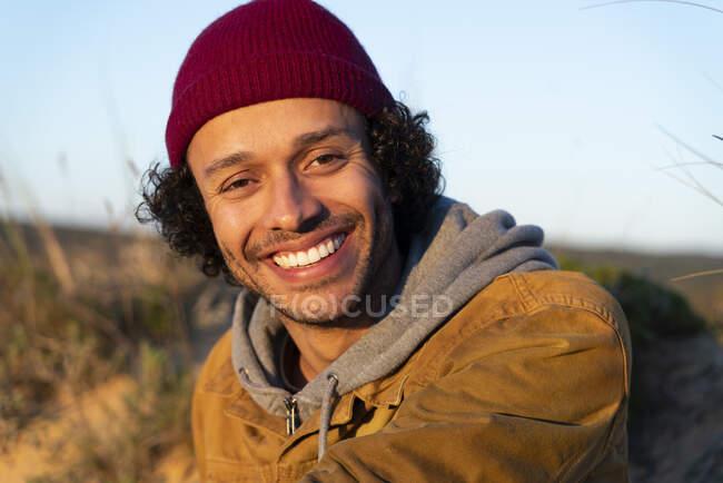 Joven con sombrero de punto sonriendo mientras está sentado al aire libre - foto de stock