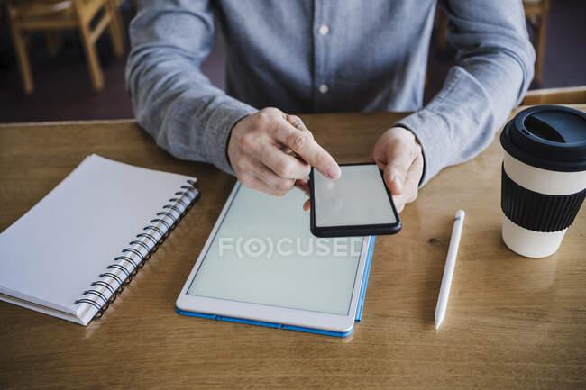 Hombre de negocios que trabaja en el teléfono móvil y la tableta digital en el lugar de trabajo - foto de stock