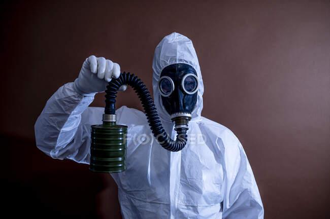 Maduro em macacões de proteção segurando tubo de máscara de gás — Fotografia de Stock