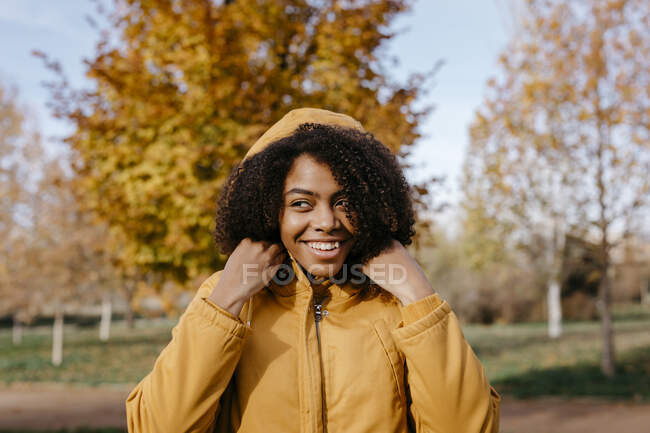Mujer joven sonriente mirando hacia otro lado mientras está de pie en el parque durante el día soleado - foto de stock