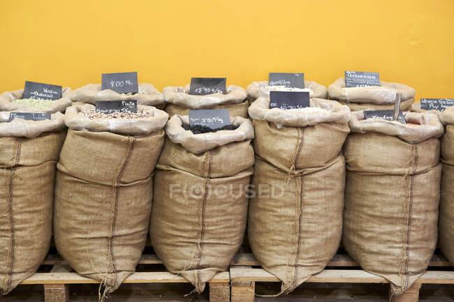 Variedades de cereales y semillas en saco almacenadas por pared - foto de stock