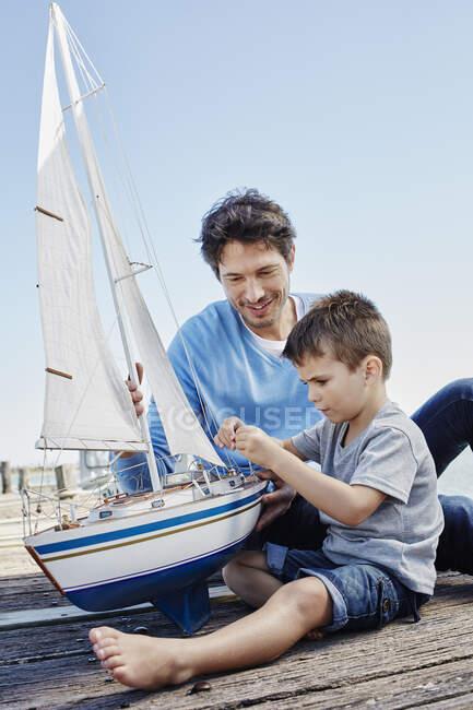 Мальчик чинит игрушечный парусник, сидя рядом с отцом на пирсе — стоковое фото