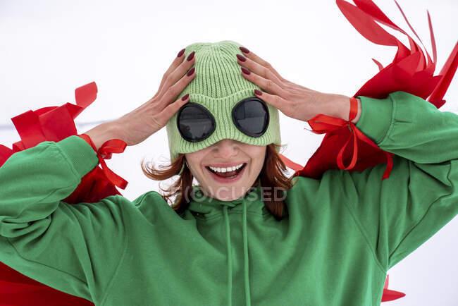 Mujer alegre con sombrero de punto verde con la cabeza en las manos contra el cielo - foto de stock